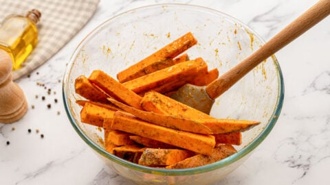 Sweet potato fries being coated in spices