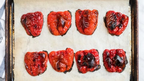 Roasted red peppers on a baking sheet