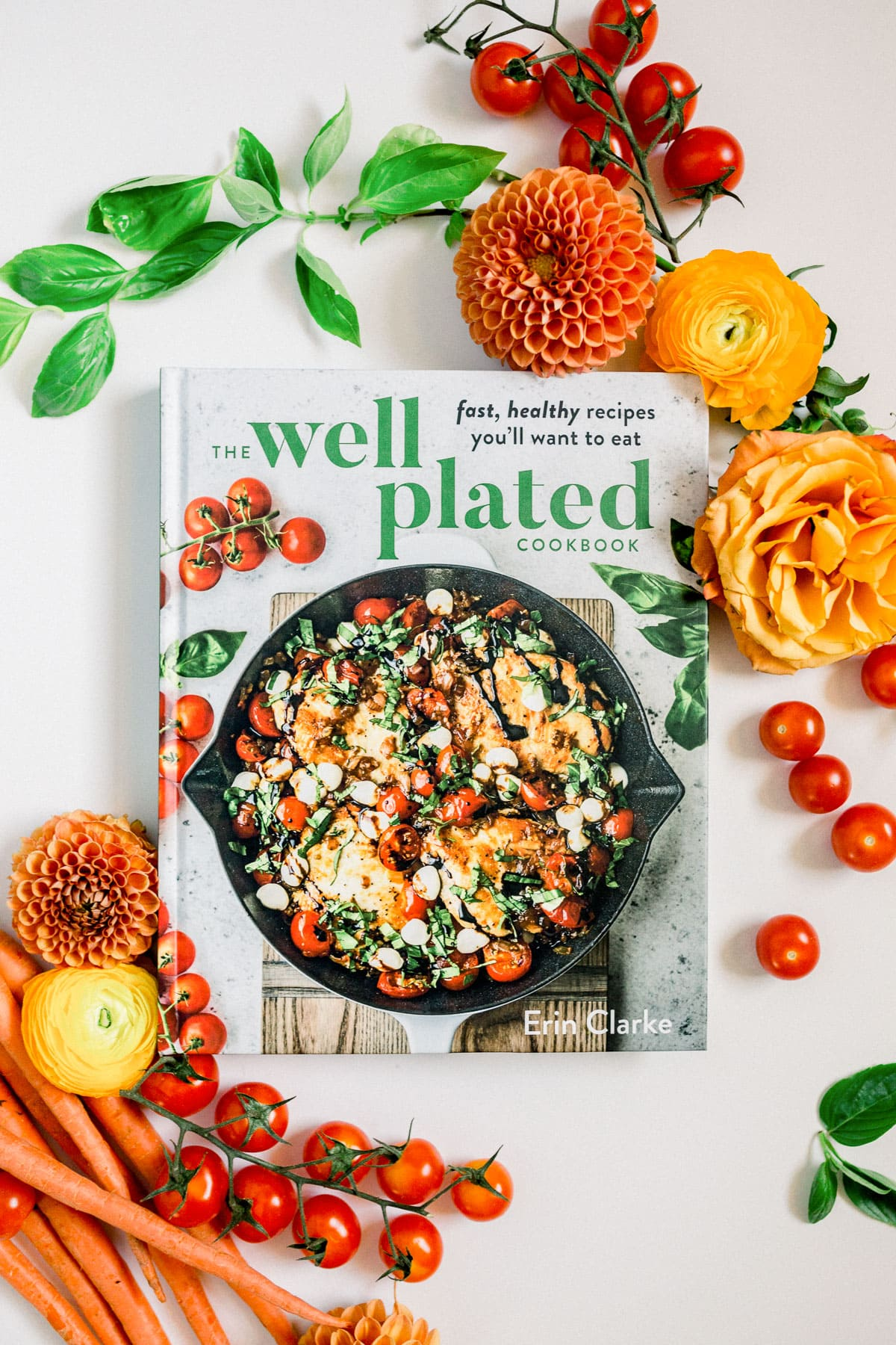 The Well Plated Cookbook on a table with flowers