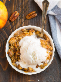 A bowl of gluten free apple crisp with vanilla ice cream
