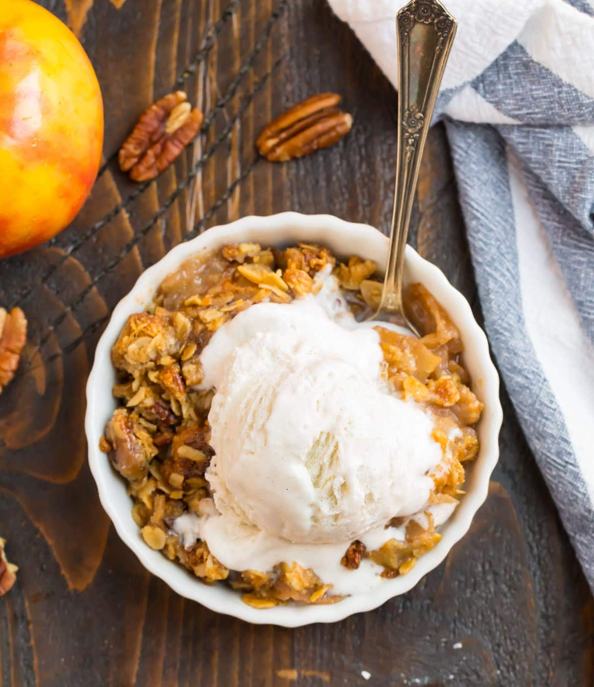 A bowl of gluten free apple crisp with vanilla ice cream