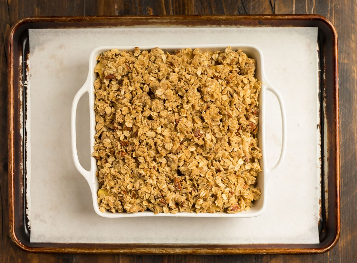 A baking dish with apple crisp on a baking sheet