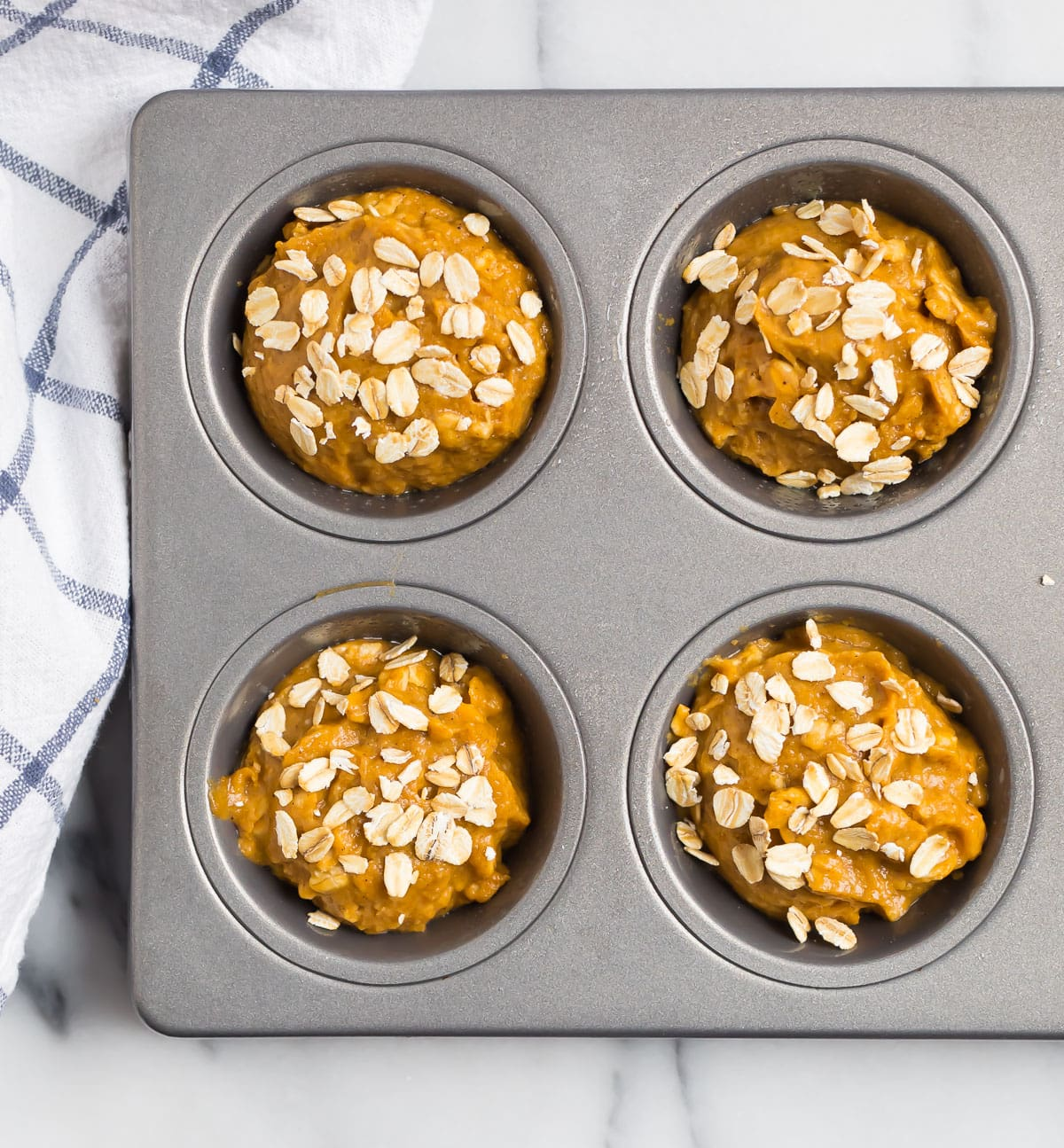 Batter in a muffin pan with oats