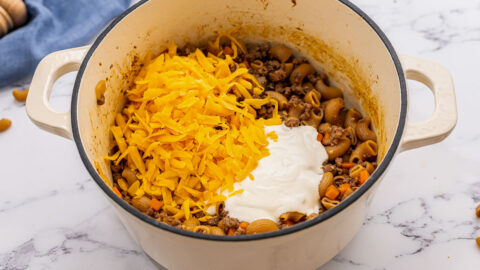 Cheese on top of ingredients in a Dutch oven