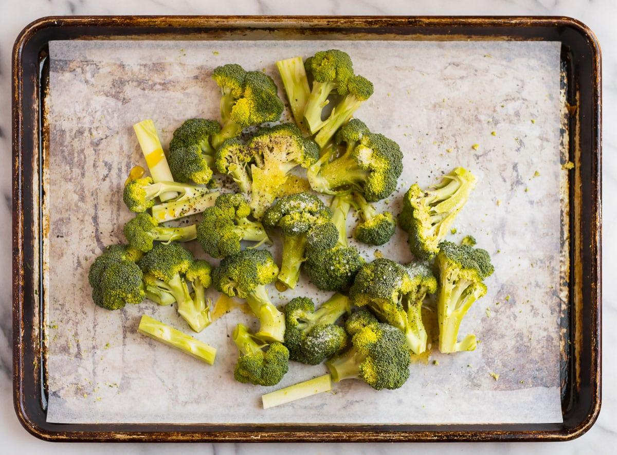 Seasoned broccoli on a sheet pan