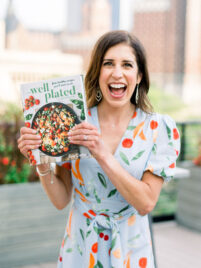 Erin Clarke holding The Well Plated Cookbook outdoors