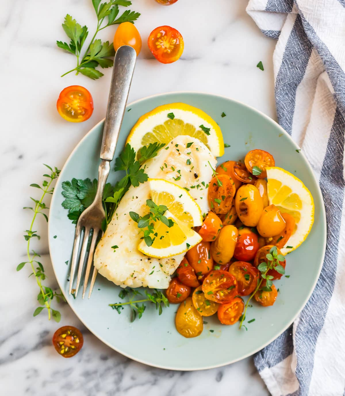 A plate of pan fried cod with tomatoes and lemon