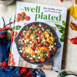 The Well Plated Cookbook with a cozy holiday blanket and candles
