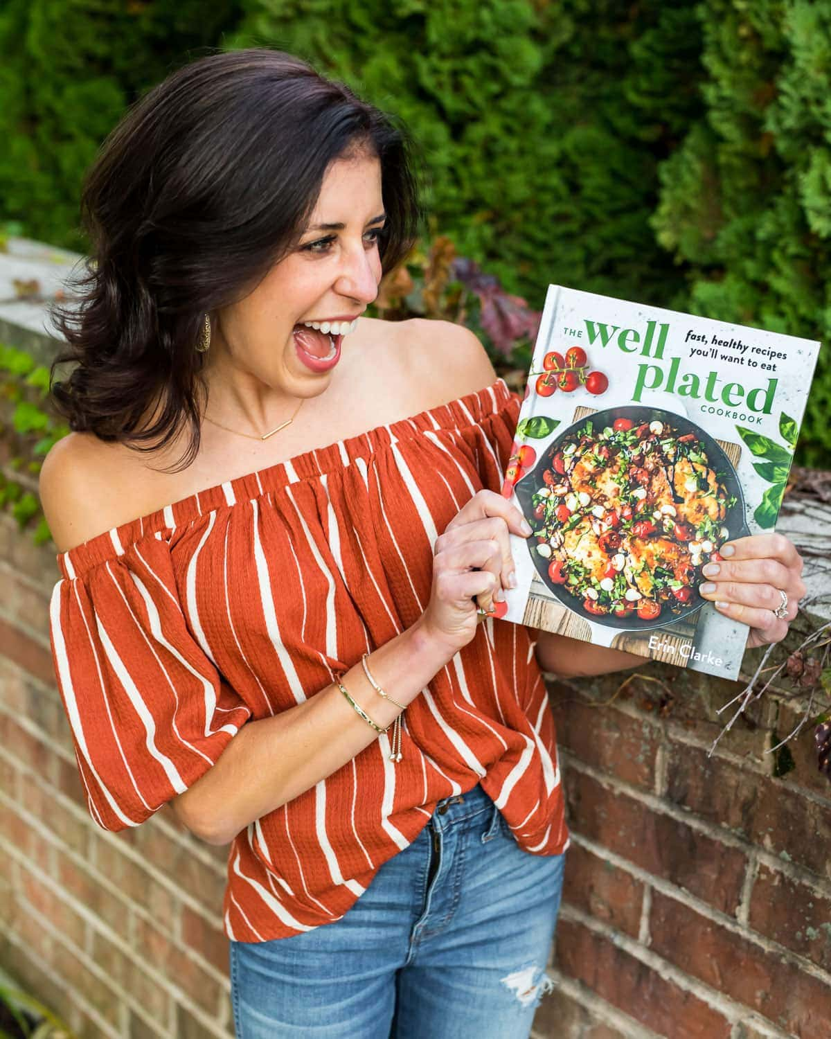 Erin Clarke holding The Well Plated Cookbook to promote a giveaway