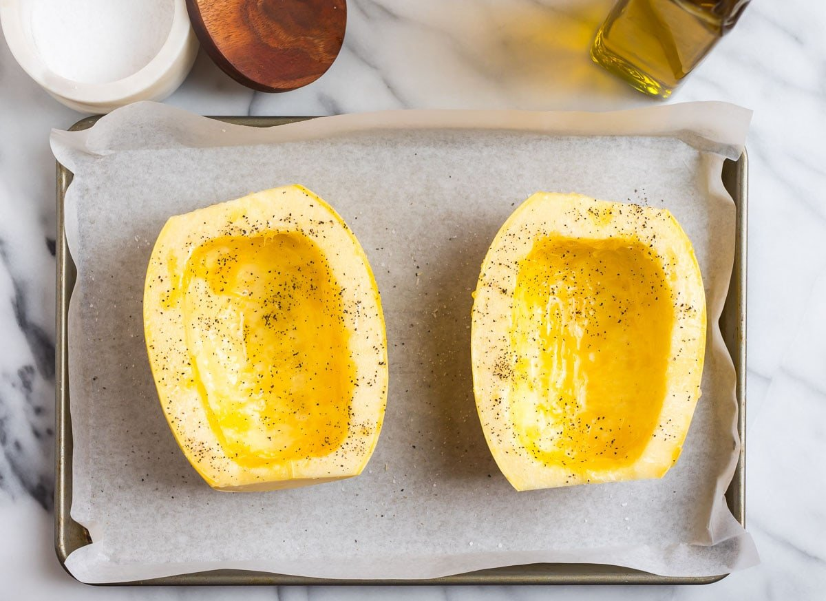 Two uncooked spaghetti squash halves with oil