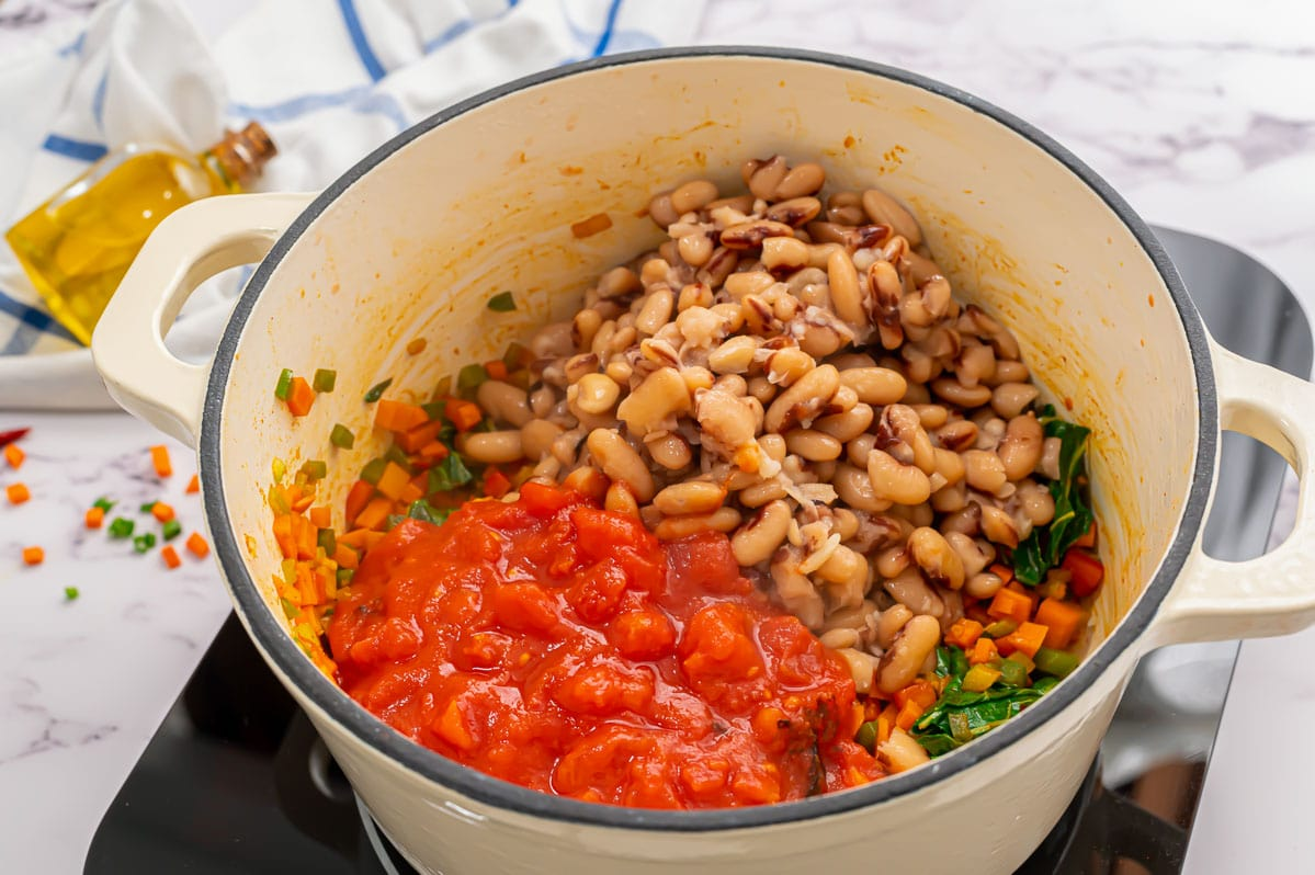 Beans, tomatoes, kale, and vegetables in a Dutch oven