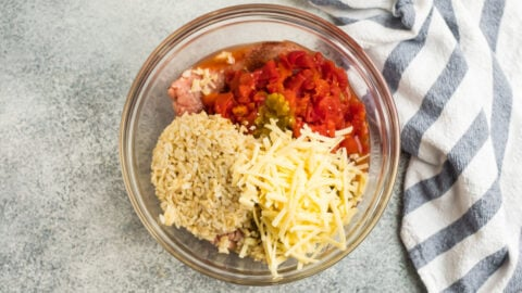 Cheese, rice, tomatoes, and meat in a bowl