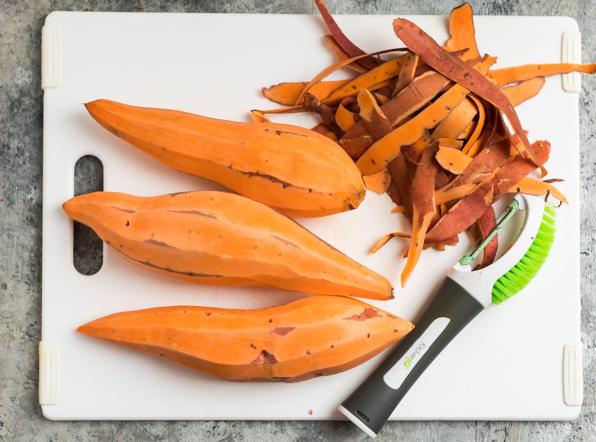 Peeled sweet potatoes on a cutting board