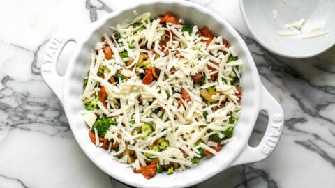Cheese scattered on top of bacon and vegetables