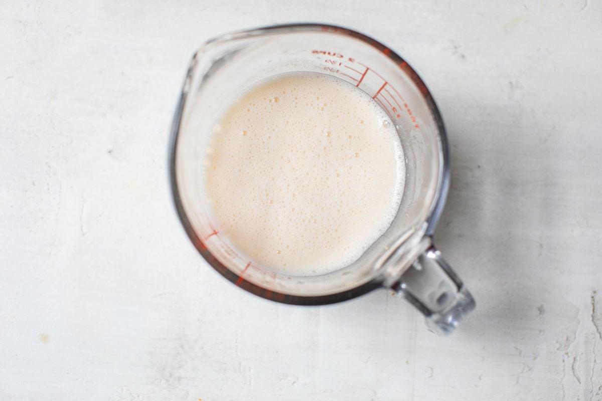 Una taza medidora con jugo de naranja y leche.