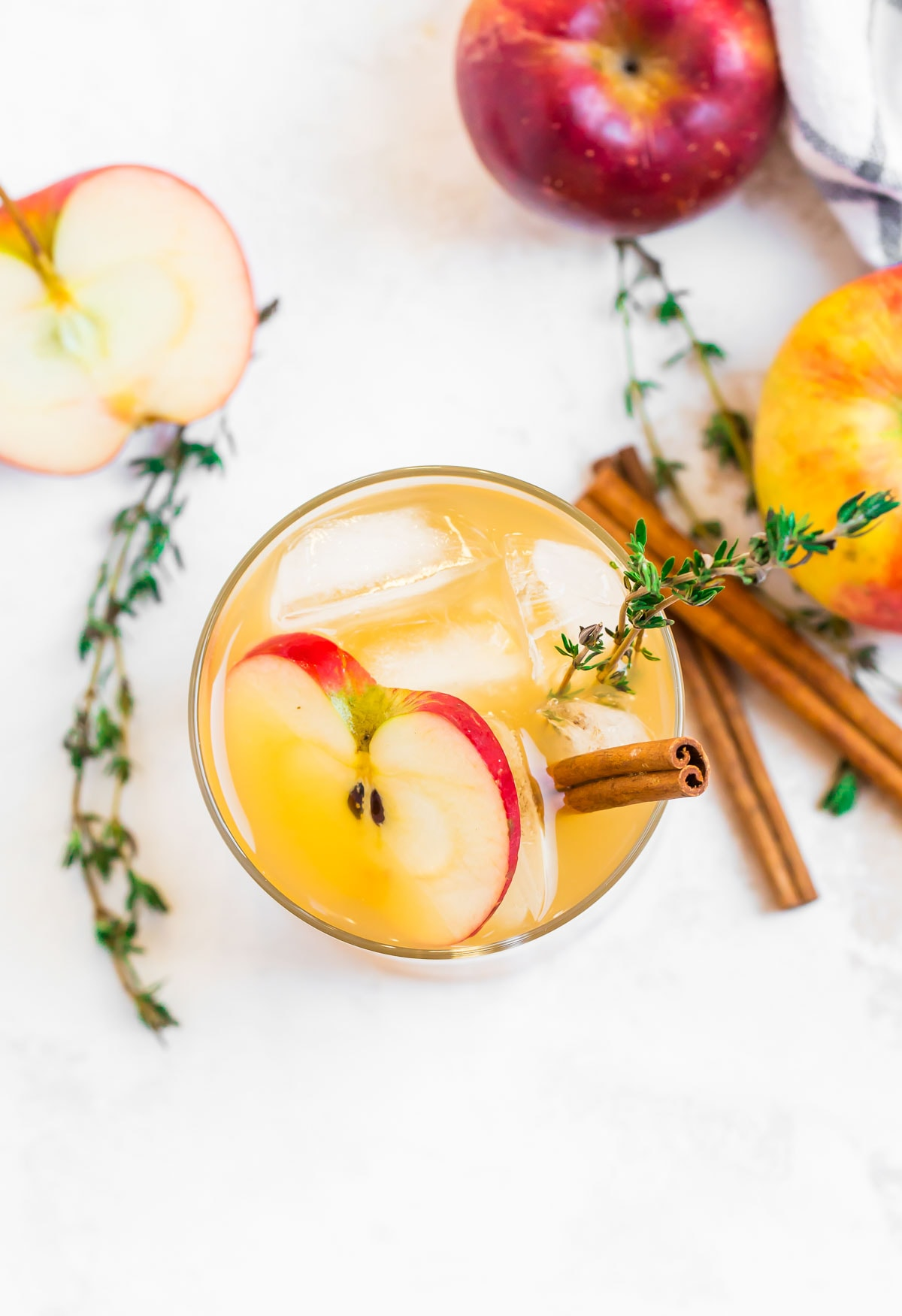 A drink in a glass next to apples and cinnamon sticks