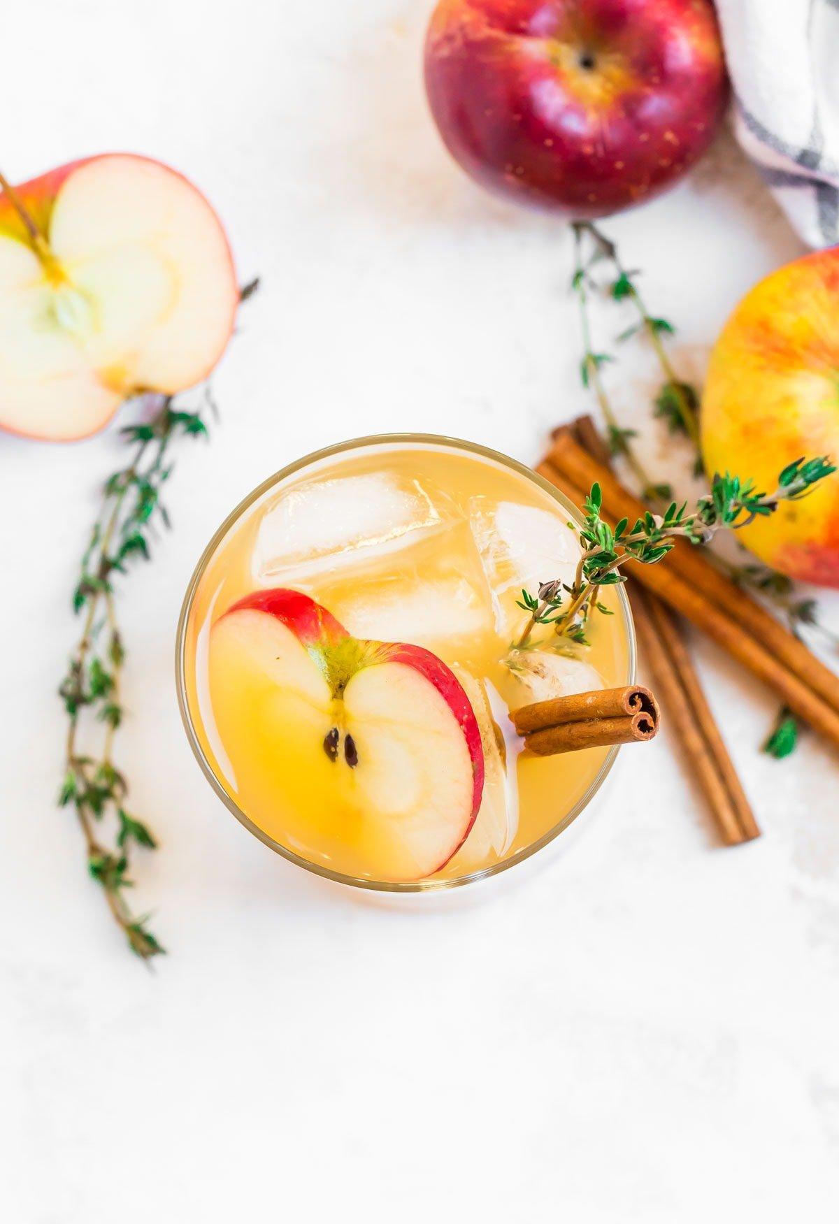 Una bebida en un vaso junto a manzanas y ramitas de canela.