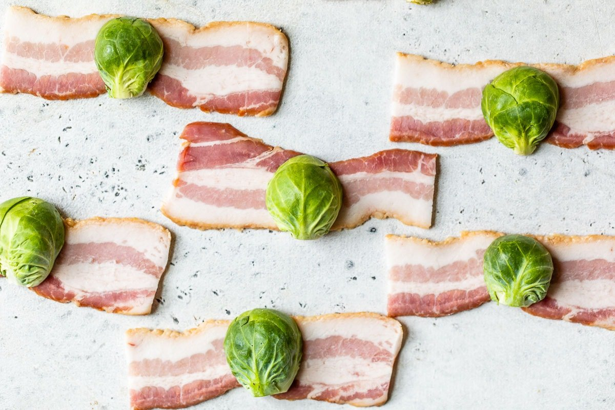 Brussels sprouts being wrapped in bacon