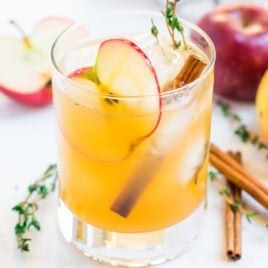 A glass of apple cider cocktail with an apple slice
