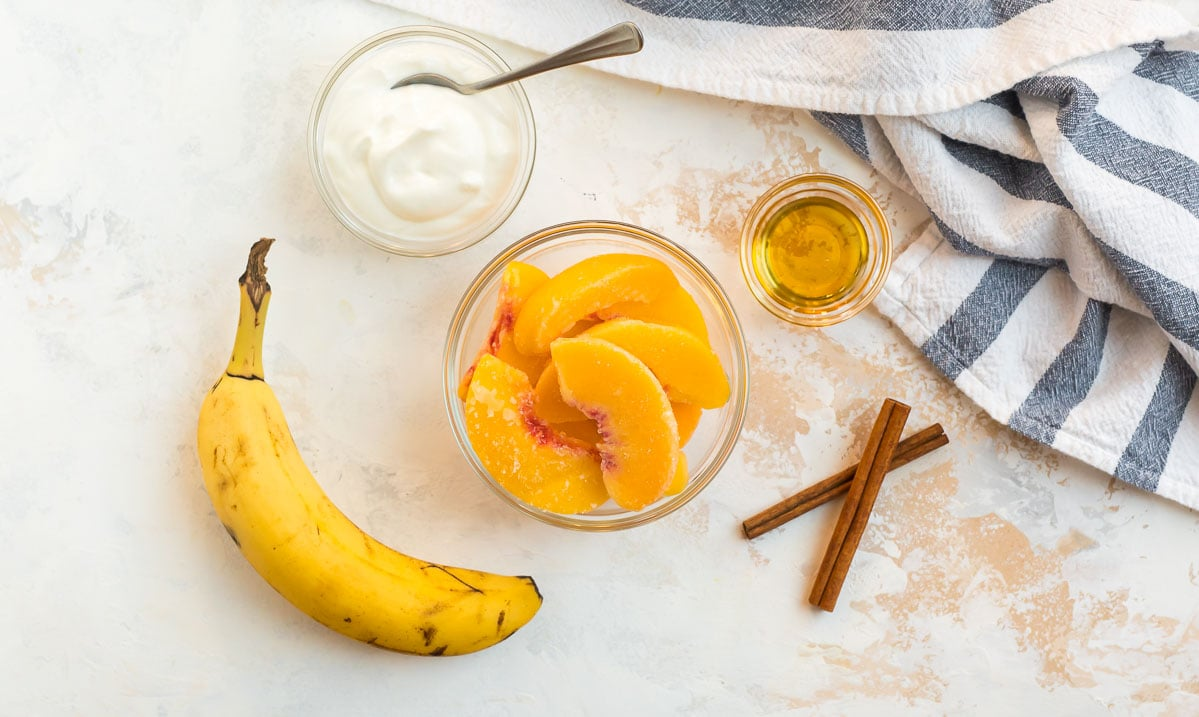 Greek yogurt, honey, cinnamon sticks, a banana, and peaches