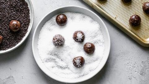 Bourbon balls being rolled in sugar