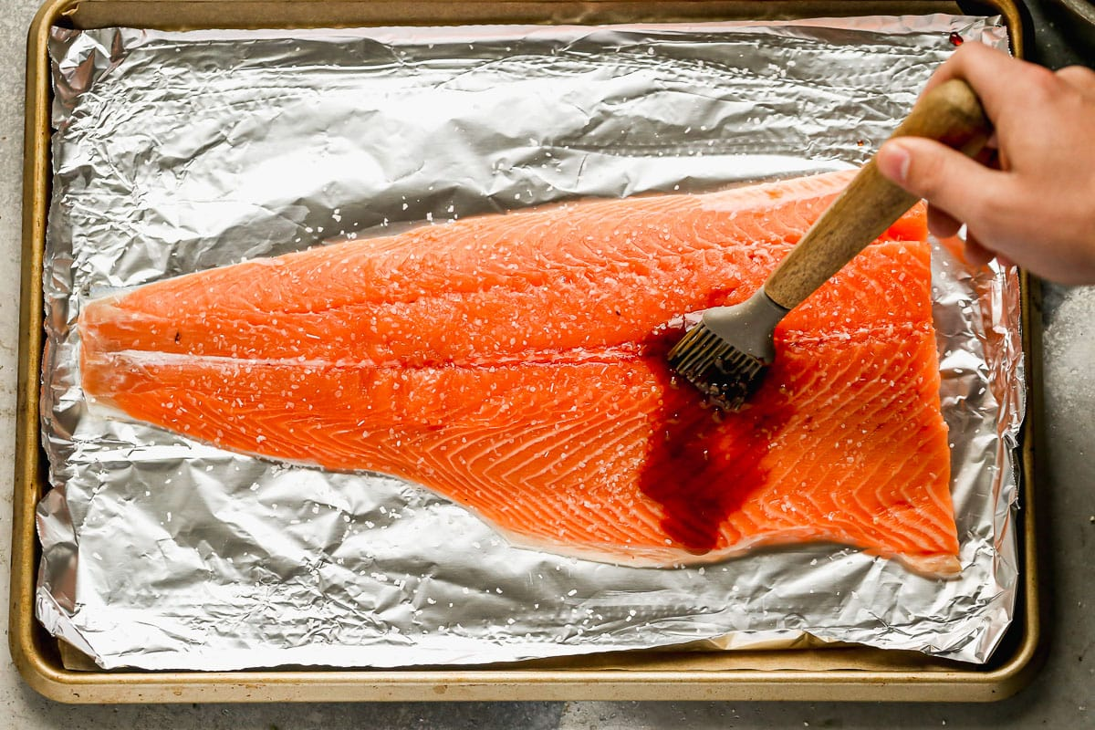 Glaze being brushed on a piece of salmon