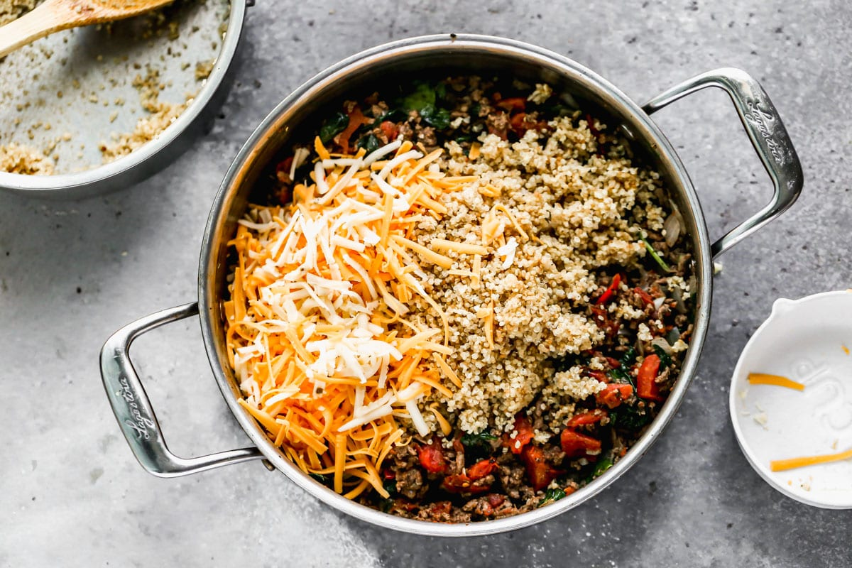 Cheese and quinoa being added to a skillet of ground beef and vegetables for stuffed peppers
