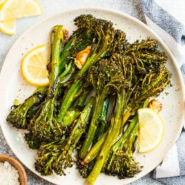 A plate of roasted broccolini with lemons