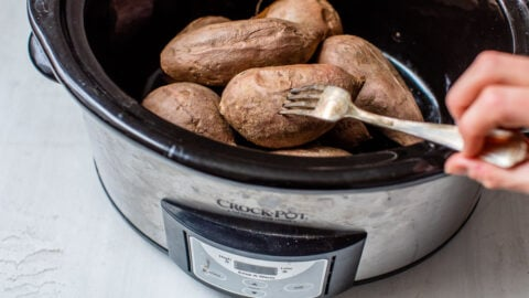 A fork piercing vegetables in a slow cooker