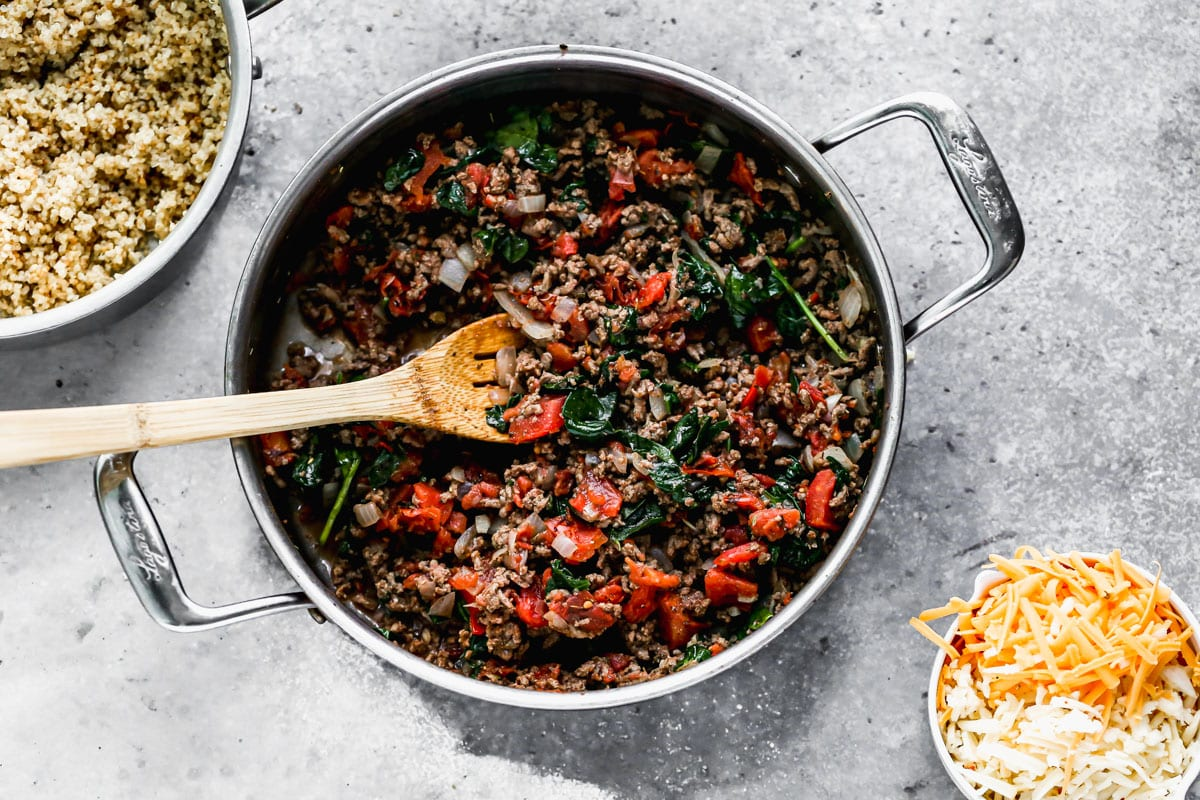A skillet with ground meat and vegetables with bowls of quinoa and shredded cheese next to it