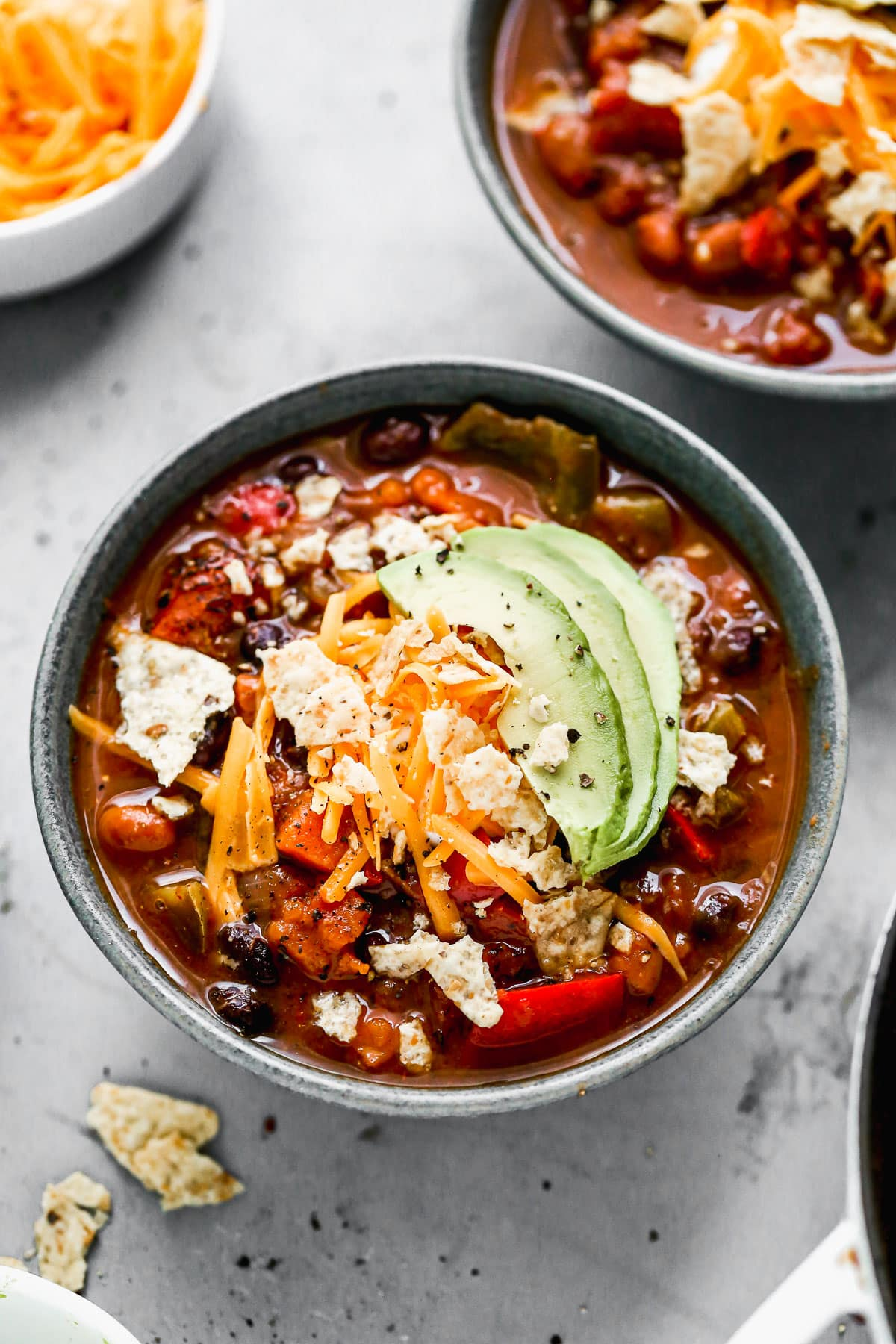 A bowl of vegetarian chili with avocado