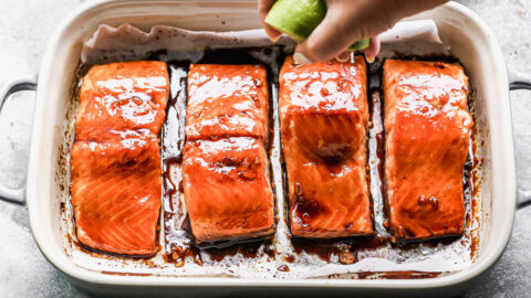 A lime being squeezed over salmon