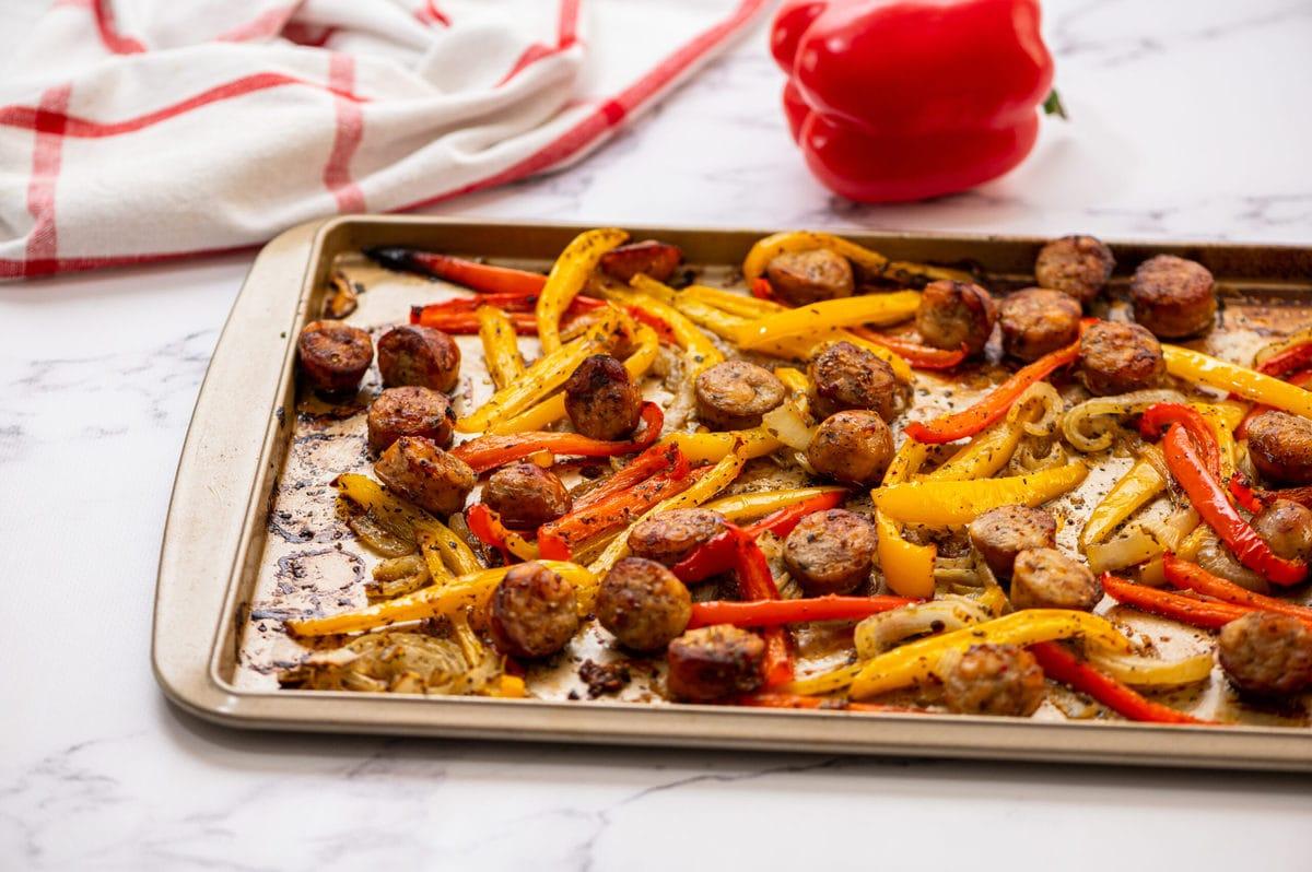 Salchicha italiana y pimientos en una bandeja para hornear