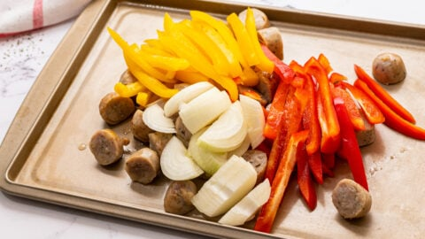 Chopped vegetables and sausage on a sheet pan
