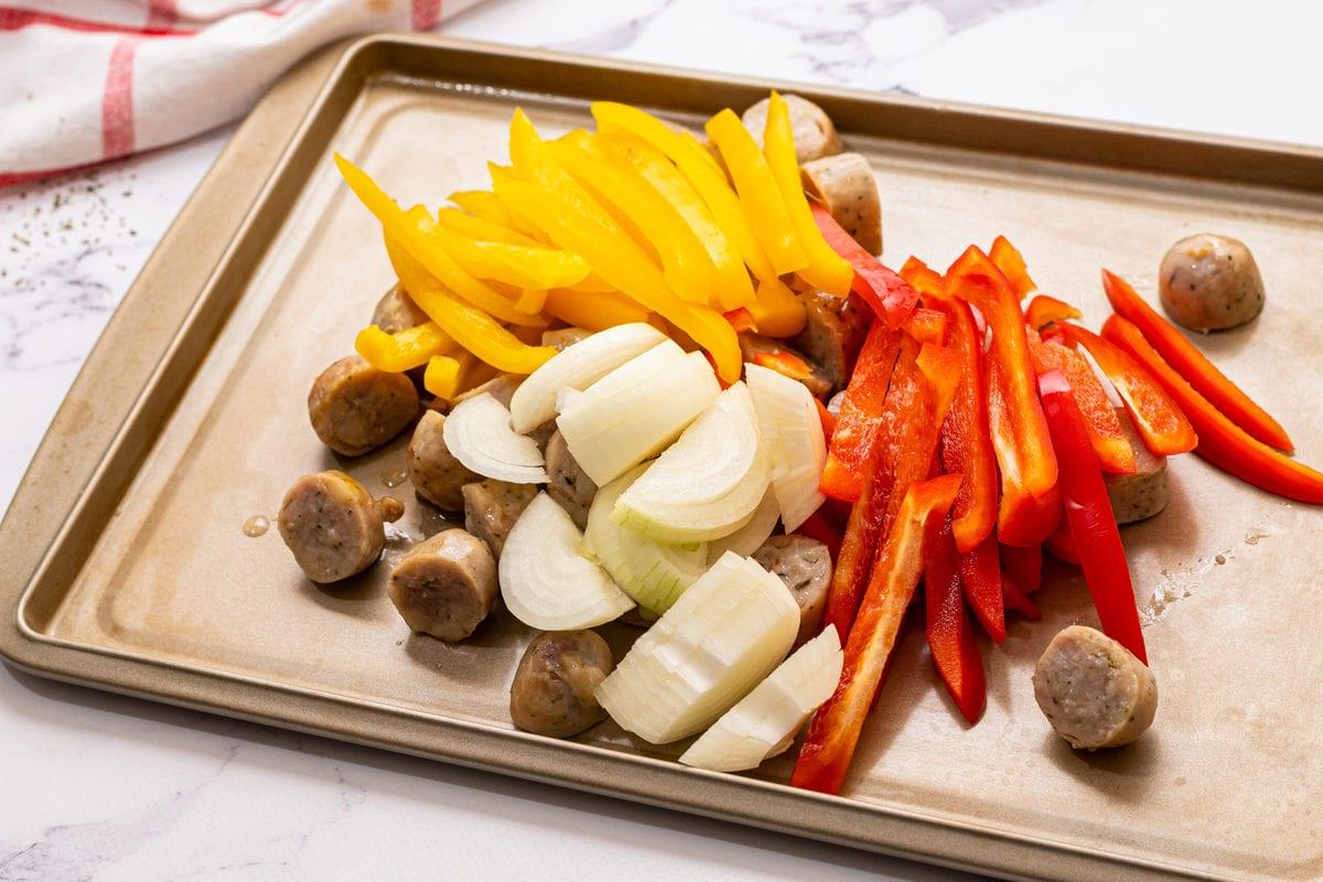 Verduras picadas y salchichas en una bandeja para hornear