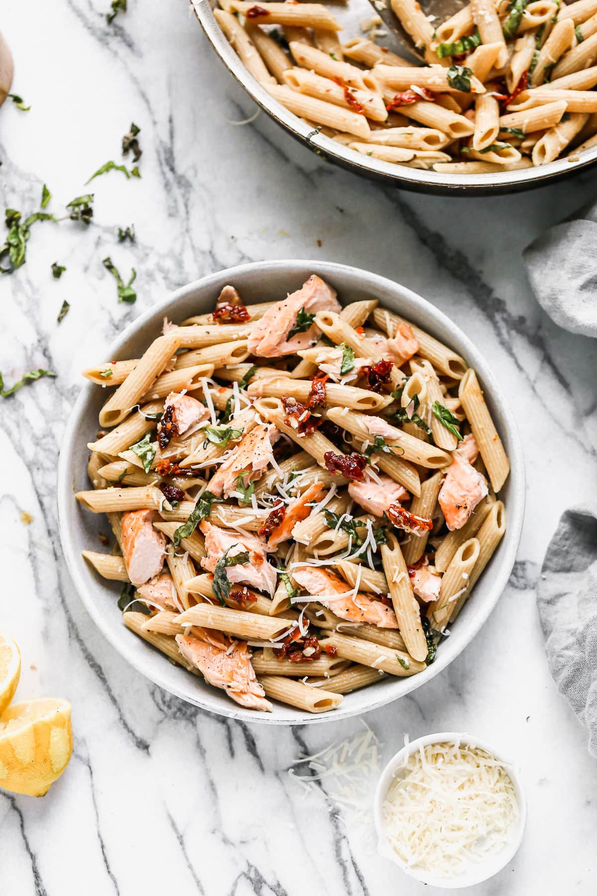Two bowls of salmon pasta with cheese