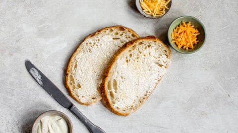 Two pieces of bread slathered in mayo and bowls of cheese
