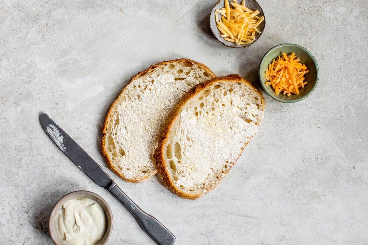 Dos piezas de pan rebozado con mayonesa y tazones de queso