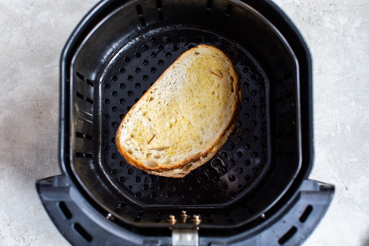 An uncooked sandwich in the basket of an appliance