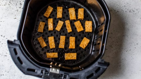Tofu pieces in an air fryer basket
