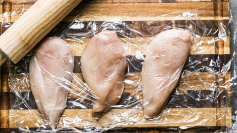 Raw chicken breasts in plastic wrap on a cutting board
