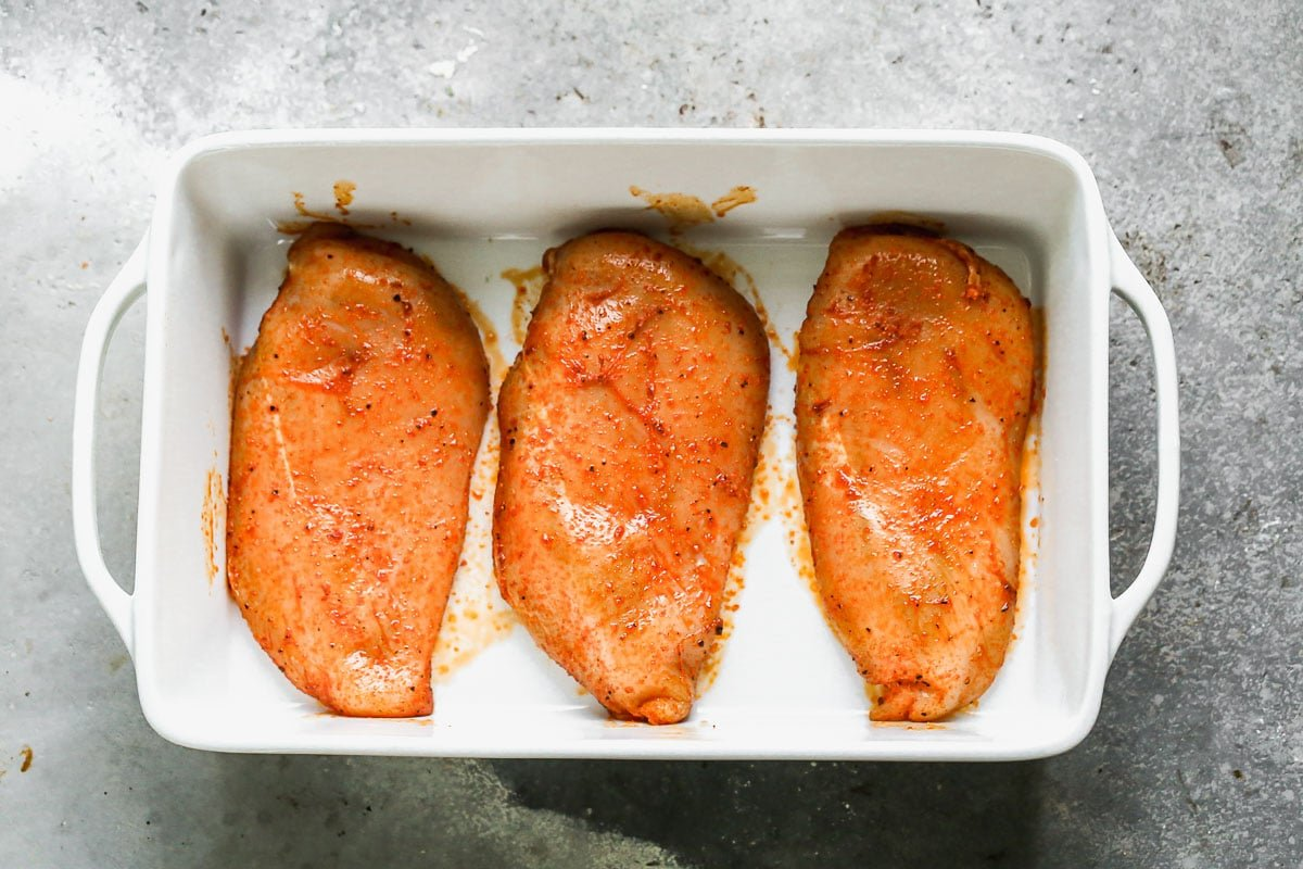 Three raw pieces of meat in a baking dish