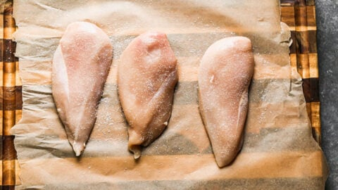 Three chicken breasts on a cutting board