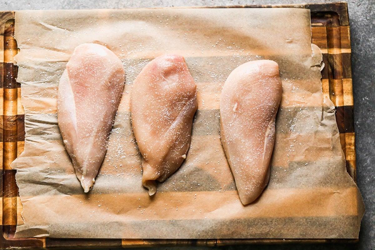 Three chicken breasts on a cutting board