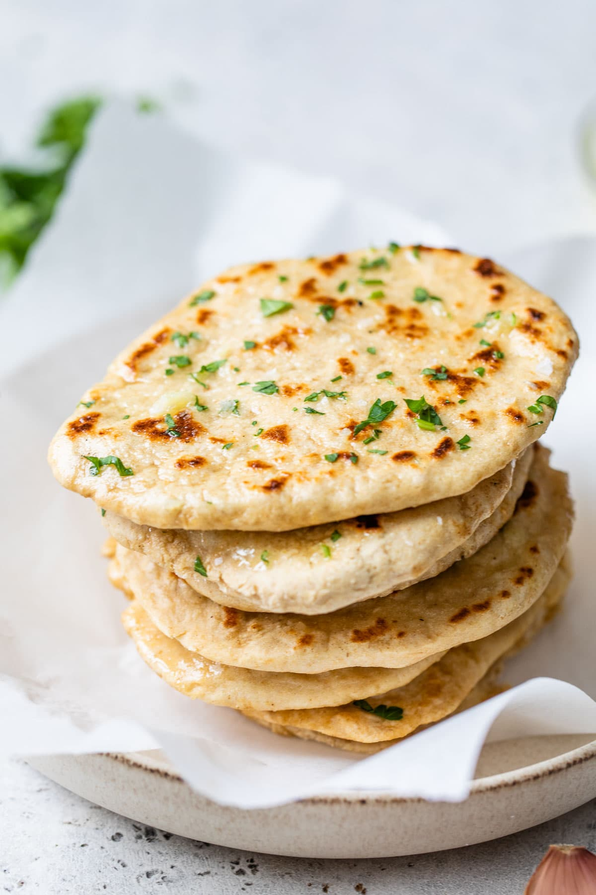 Homemade naan bread in a stack with butter