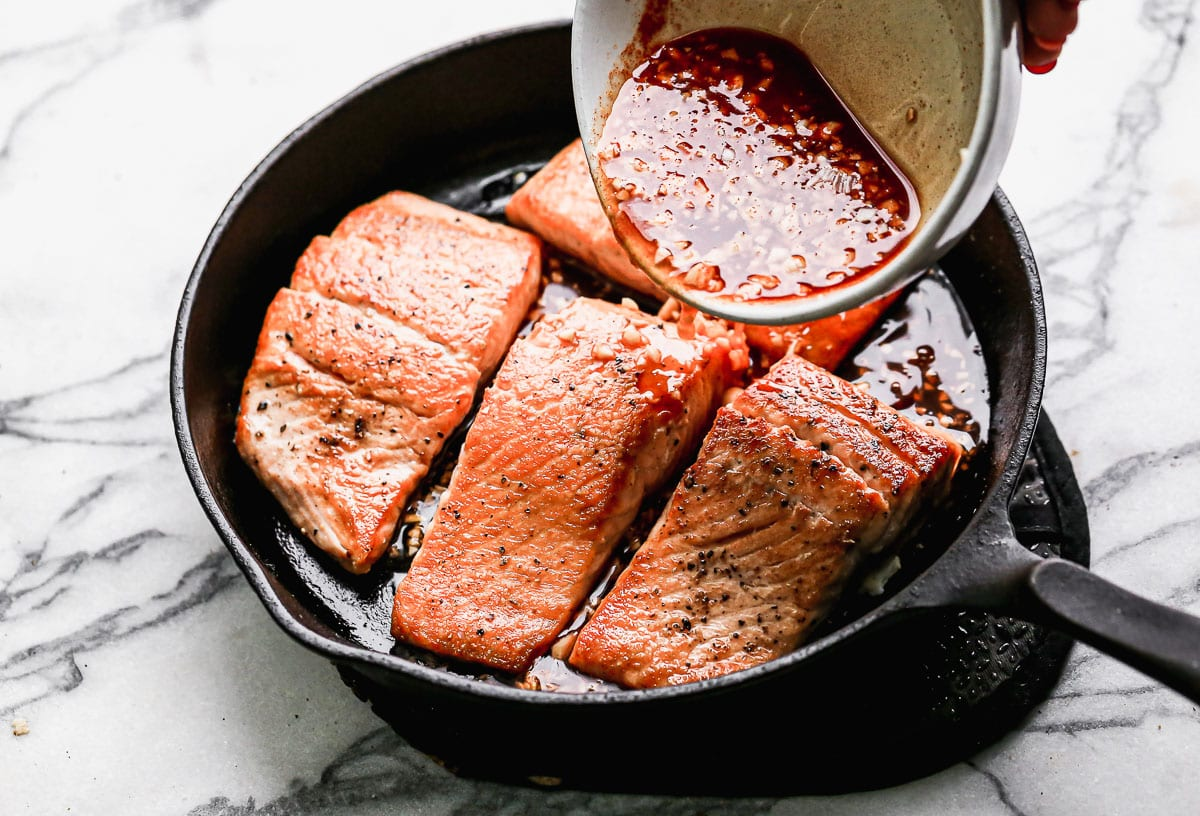 Sauce being poured over salmon fillets
