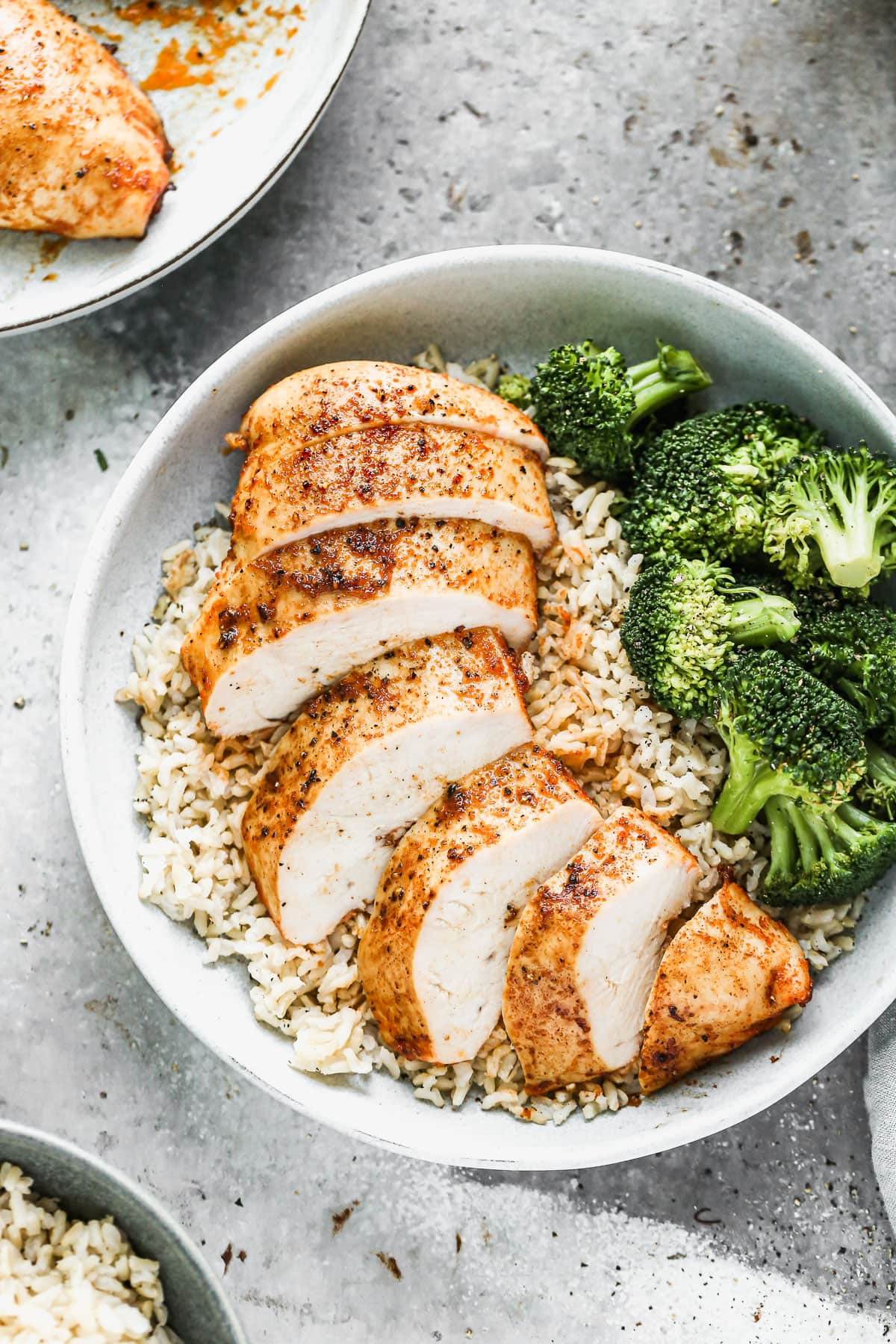 A sliced chicken breast with rice and broccoli