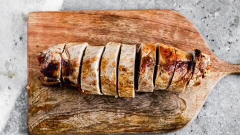 Cooked pork tenderloin on a cutting board