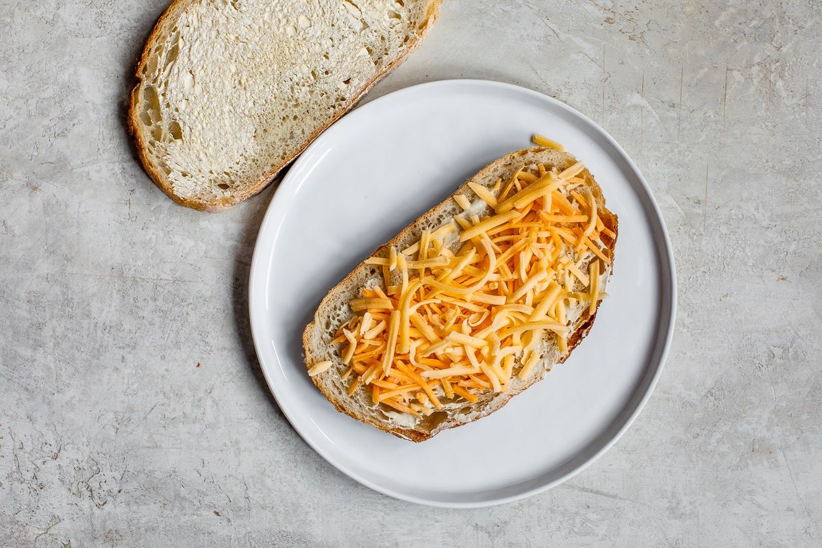 Shredded cheese on a piece of bread