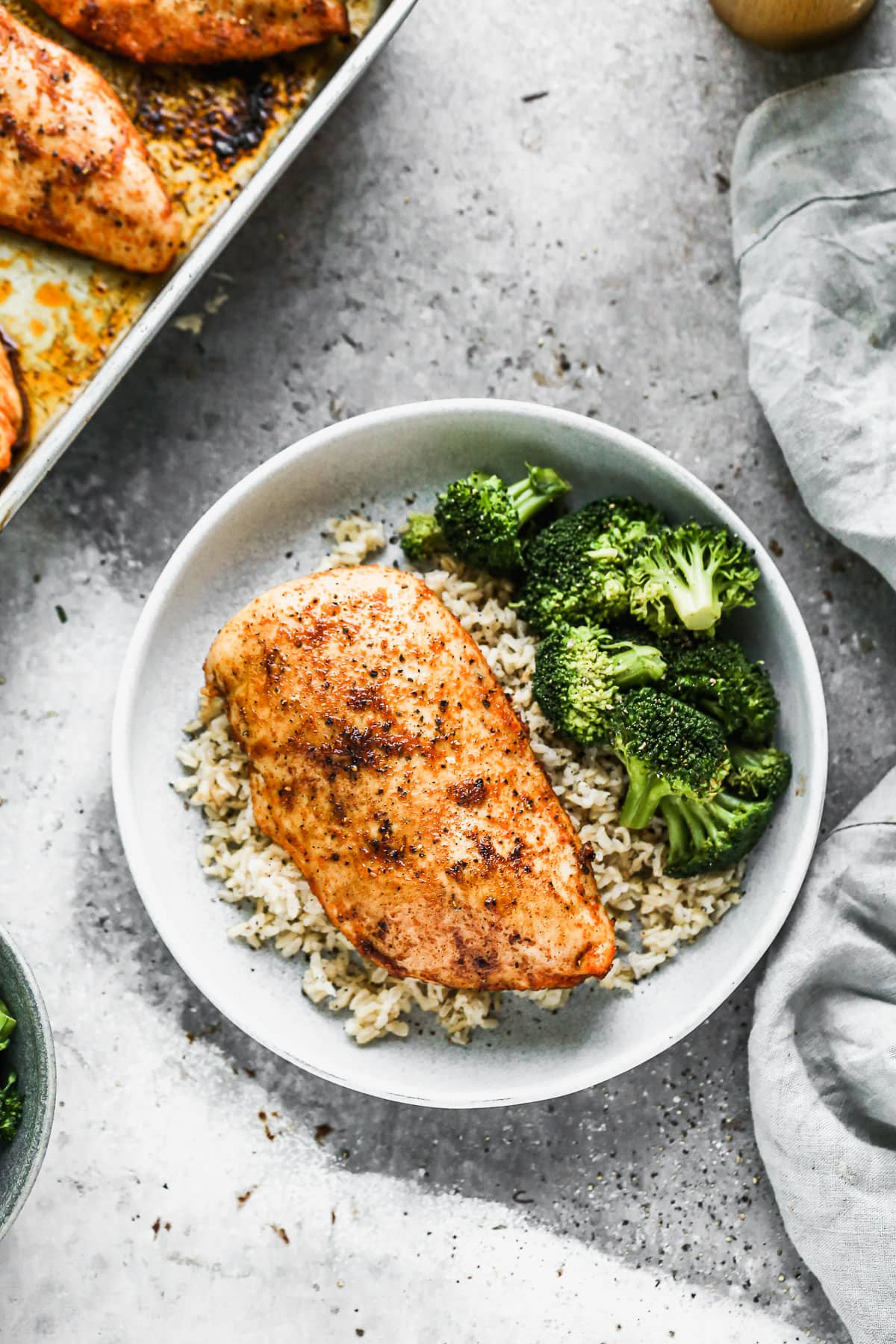 Oven roasted chicken breast in a bowl with rice and broccoli